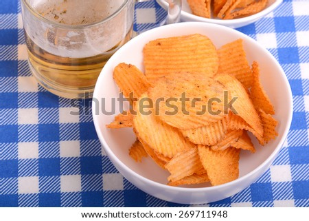 Glass of light beer and potato chips on white plate - stock photo
