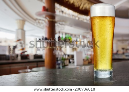 Glass of light beer in a pub. - stock photo