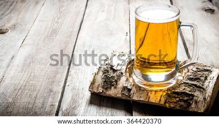 Glass of light beer on a birch stand . On a wooden table. - stock photo