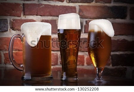 Glass of light beer on a dark pub - stock photo
