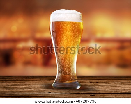 Glass of light beer on a dark pub, bar, with wood table and orange background with bokeh effect