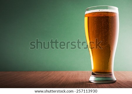 Glass of light beer on blue background - stock photo
