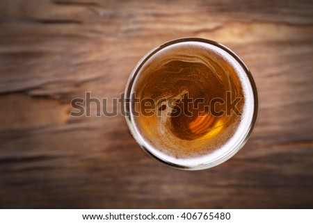 Glass of light beer on wooden background - stock photo
