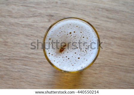 Glass of light beer on wooden background, top view - stock photo