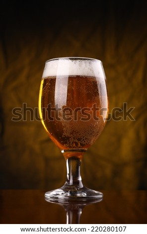 Glass of light beer over a yellow lit cloth background