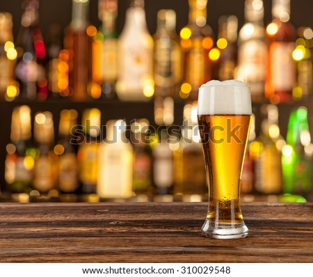 Glass of light beer served on wooden desk. Bar on background - stock photo