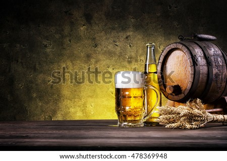 Glass of light beer with bottle and barrel on yellow background