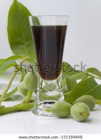 Glass of liqueur from young green walnuts-Juglans regia - stock photo