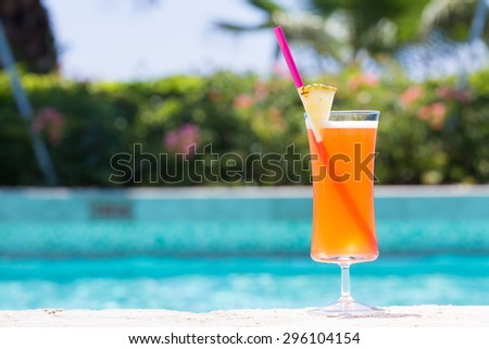 Glass of Mai Tai cocktail on the pool nosing at the tropical resort. Horizontal, cocktail on right side - stock photo