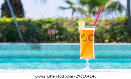 Glass of Mai Tai cocktail on the pool nosing at the tropical resort. Horizontal, wide screen, cocktail on right side - stock photo