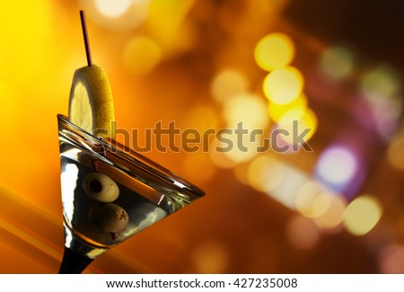 Glass of martini with lemon and green olives  - stock photo