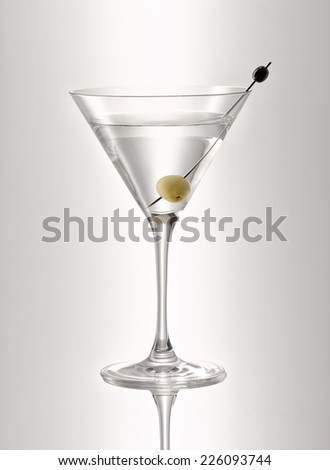 glass of martini with olive - stock photo
