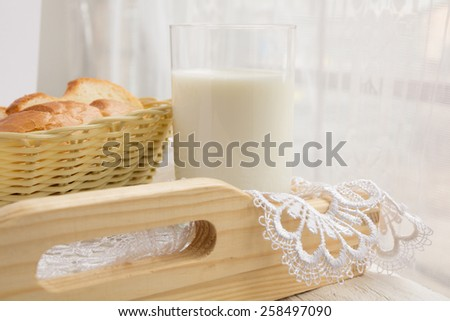 Glass of milk and a basket of bread on the background of a window - stock photo