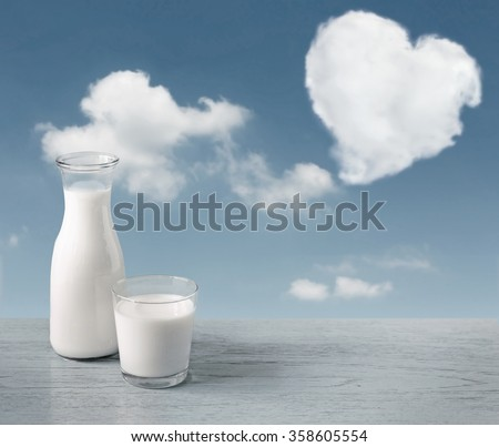 glass of milk and a milk bottle on a wooden table background, sky, clouds heart. - stock photo