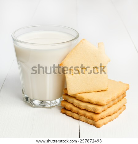 Glass of milk and biscuits with sign EAT ME against white wooden background