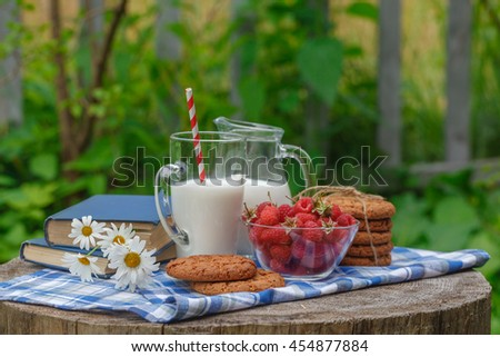 glass of milk and bowl of fresh berries in an outdoor setting, healthy breakfast in the garden - stock photo