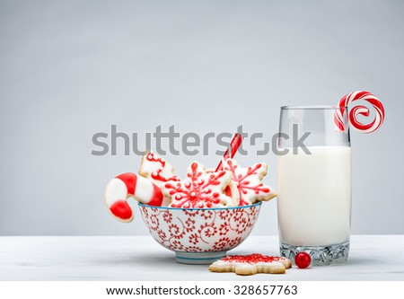 Glass of Milk, and bowl of red and white sugar cookies for Santa over a white background.
