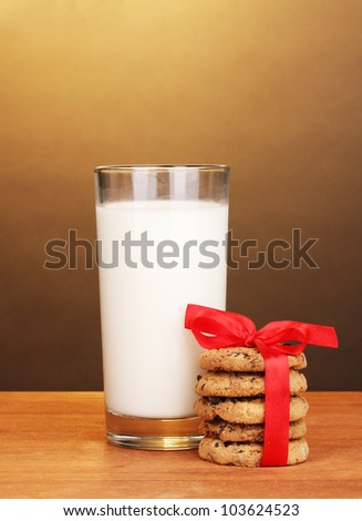 Glass of milk and cookies on wooden table on brown background