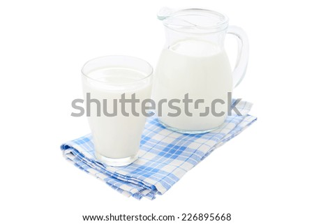 Glass of milk and jug on blue checkered tablecloth on white background - stock photo