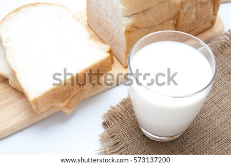 glass of milk and sliced bread on white background