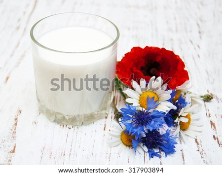 Glass of milk and wildflowers on a old wooden background - stock photo