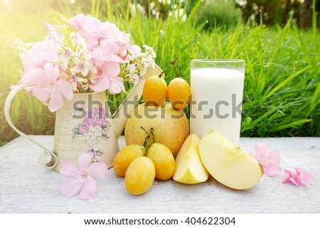 glass of milk, apple fruit and pink flower on white wood table with green grass nature background in a garden  - stock photo