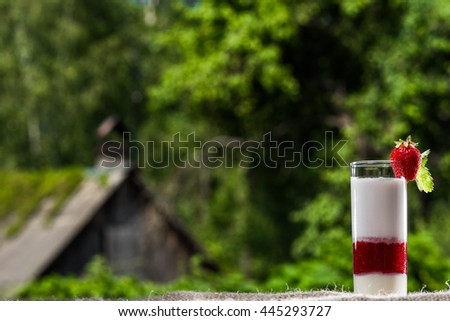 Glass of milk cocktail and fresh strawberries over the summer foliage background.