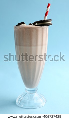 Glass of milk cocktail with chocolate cookies on blue background - stock photo