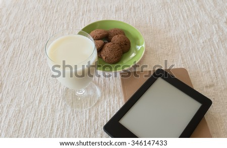 Glass of milk, cookies, notebook and ebooks reader on fabric.