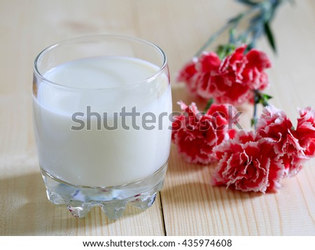 Glass of milk for breakfast and carnation flowers on wooden table - stock photo