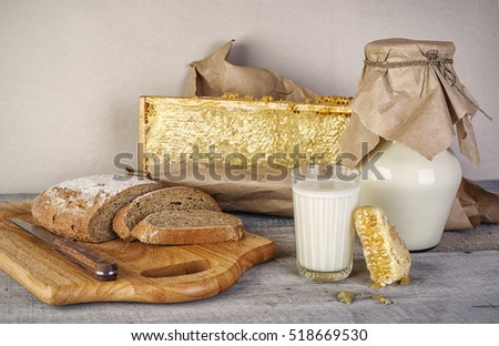 glass of milk fresh bread and honeycomb on wooden table