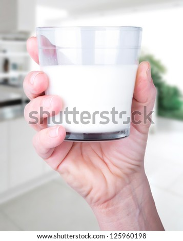 Glass of milk in hand in the kitchen - stock photo