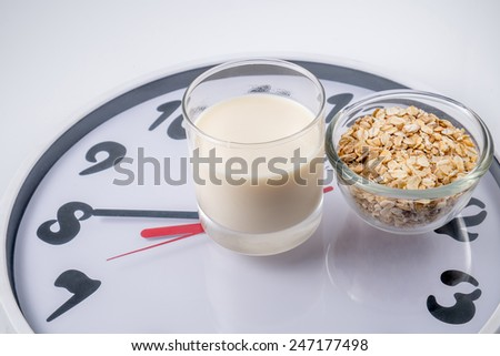 Glass of milk, oat and clock. Healthy breakfast concept. - stock photo