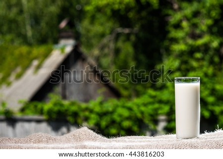 Glass of milk on burlap over foliage background.