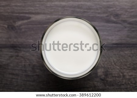 Glass of milk on wooden table - stock photo