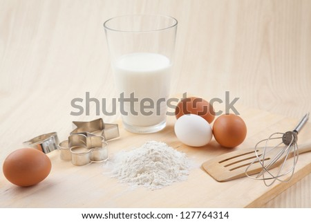 glass of milk, whisk, Cookie cutter forms and eggs on wooden table together