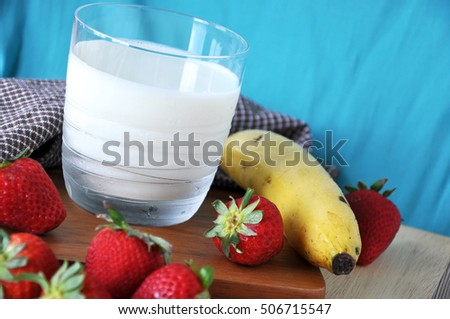 Glass of milk with banana and strawberries on blue background