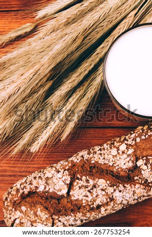 Glass of milk with breaf lying on wooden table - stock photo
