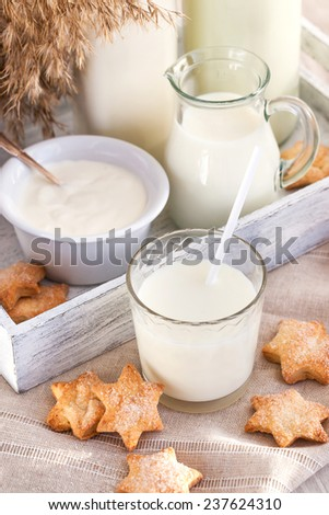 Glass of milk with cookies and bootles on the background