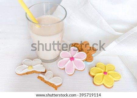 Glass of milk with cookies. Flower shaped colorful cookies on white wooden background. Closeup with shallow dof - stock photo