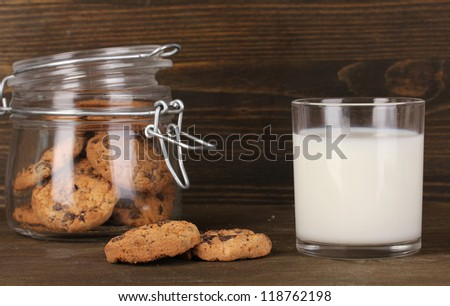 Glass of milk with cookies on wooden table close-up - stock photo