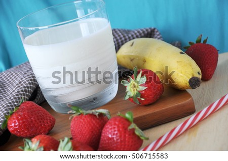 Glass of milk with fresh strawberries and banana on wooden board