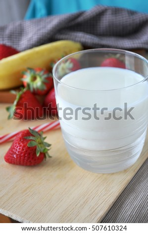 Glass of milk with fresh strawberries on wooden background