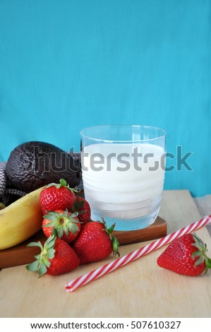 Glass of milk with healthy fruits on blue background