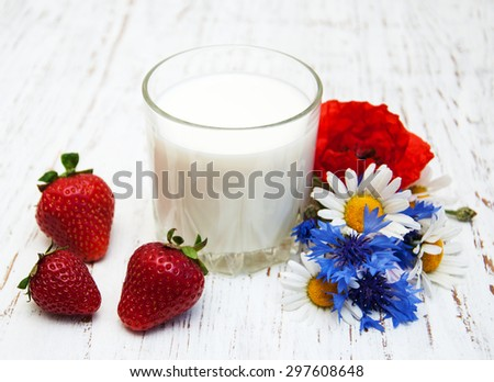Glass of milk with strawberry and wildflowers on a old wooden background - stock photo