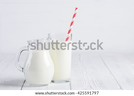 Glass of milk with stripped red paper straw and jug of milk on white wooden table