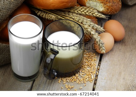 Glass of milk with wheat bread and chicken eggs - stock photo