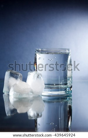 Glass of mineral water near ice cubes on dark background - stock photo