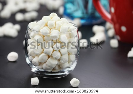 Glass of mini marshmallows with cup of cocoa in the background. Extreme shallow depth of field. - stock photo