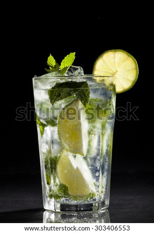 Glass of mojito cocktail on a black background.